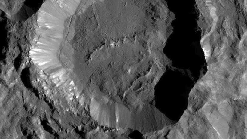 Astronomie: Der Krater Kupalo auf dem Zwergplaneten Ceres. Der etwa 25 Kilometer breite Krater ist vergleichsweise jung, wie seine noch wenig verwitterte Oberfläche und besonders die scharfen Kanten am Rand verraten. Die hellen Flecken dürften Salzablagerungen sein, die aus unterirdischem Eis stammen.