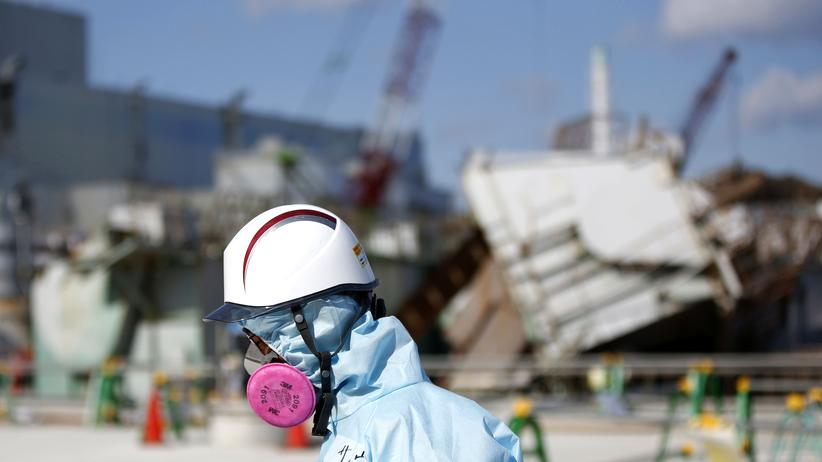 Fukushima-Jahrestag: Ein Arbeiter im Februar 2016 auf der Anlage des havarierten AKW Fukushima-Daiichi: Im Hintergrund ist der Reaktorblock 1 zu erkennen. Seine Hülle flog vor fünf Jahren als erstes in die Luft.
