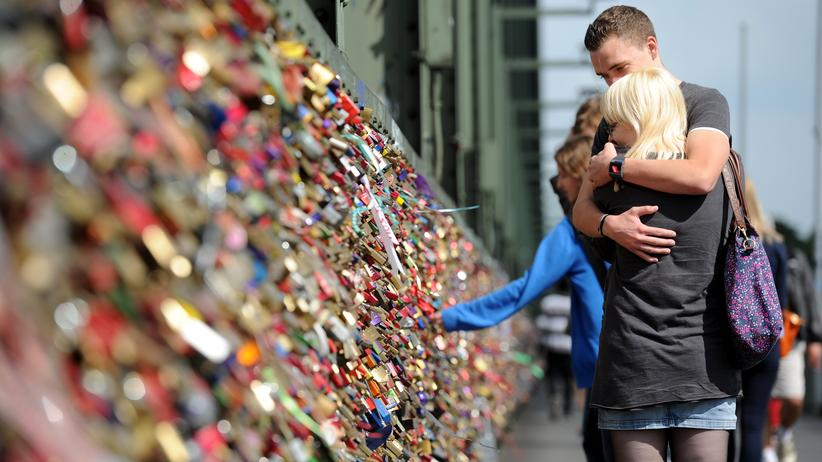 Partnerschaft: Ein Paar umarmt sich auf einer Brücke, an deren Geländer Liebesschlösser hängen.