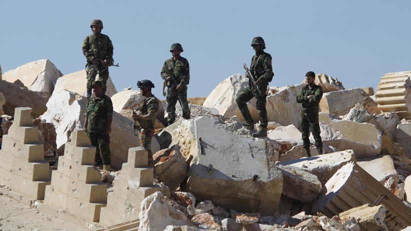 """Jordanien: Soldaten der syrischen Armee stehen auf den Ruinen des Baal-Tempels der antiken Stadt Palmyra, die die Terrororganisation """"Islamischer Staat"""" zerstört hatte. Geht es nach dem Deutschen Archäologischen Institut soll sich eine solche Tragödie nicht wiederholen."""