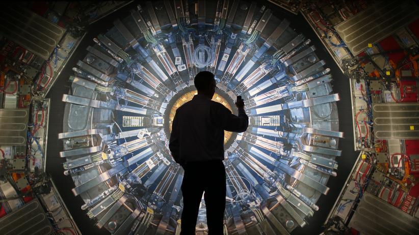 Quantenmechanik: Was passiert im Kern? Ein Besucher einer Ausstellung vor einem Bild des Teilchenbeschleunigers LHC