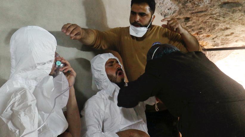Giftgas in Syrien: 4. April in der von Rebellen gehaltenen Stadt Chan Scheichun im Norden Syriens: Ein Mann atmet durch eine Sauerstoffmaske, ein anderer wird behandelt. Die beiden waren vermutlich Giftgas ausgesetzt.