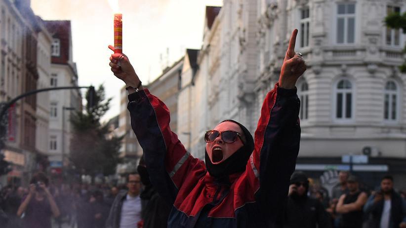 G20-Proteste: Der 7. Juli im Schanzenviertel: Eine Frau zündet während einer Anti-G20-Demonstration ein Leuchtfeuer an. Während des G20-Gipfels kam es in Hamburg an mehreren Orten zu heftigen Ausschreitungen.
