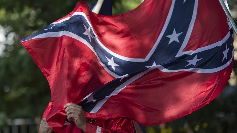 USA: Ein Mitglied des Ku Klux Clans hält sich in Charlottesville, USA, die Konföderiertenflagge vors Gesicht.