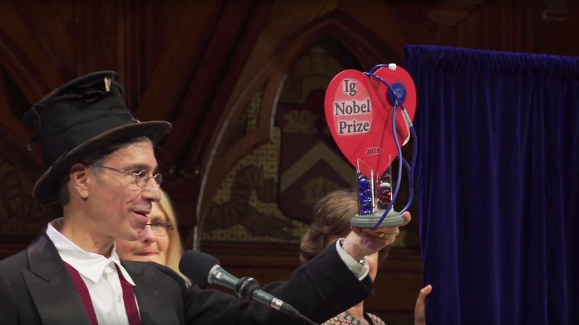 Ig-Nobelpreis: Moderator Marc Abrahams hält die Ig-Nobelpreis-Trophäe in die Höhe.