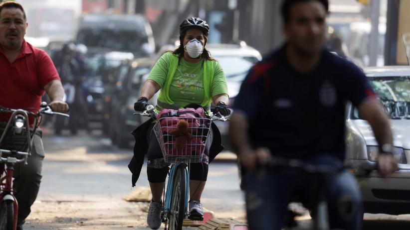 Klimawandel: Eine Radfahrerin schützt sich in Mexiko-Stadt mit einer Atemmaske vor dem Smog. Neben Ruß und anderen Schadstoffen stoßen Verbrennungsmotoren auch das klimaschädliche CO2 aus.