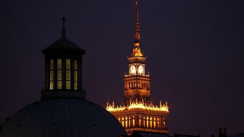 """Stalins """"Geschenk"""" an Warschau leuchtet im nächtlichen Warschau. Der Kulturpalast erinnert auf pompöse Weise an die Zeit, als Russland Polen unter seinem Stiefel hatte"""