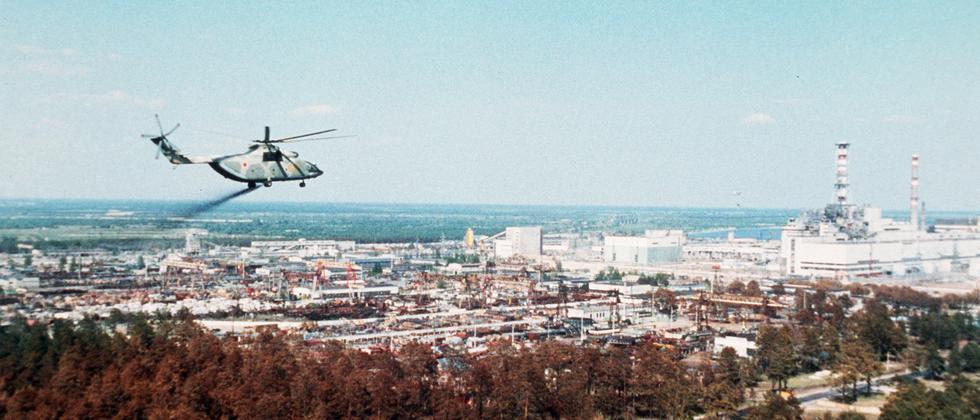 Ein Helikopter fliegt 1986 auf die Überreste des explodierten Reaktor 4 des AKW Tschernobyl zu. Dabei schüttet er Stoffe ab, die etwas gegen die radioaktiven Teilchen in der Luft ausrichten sollen