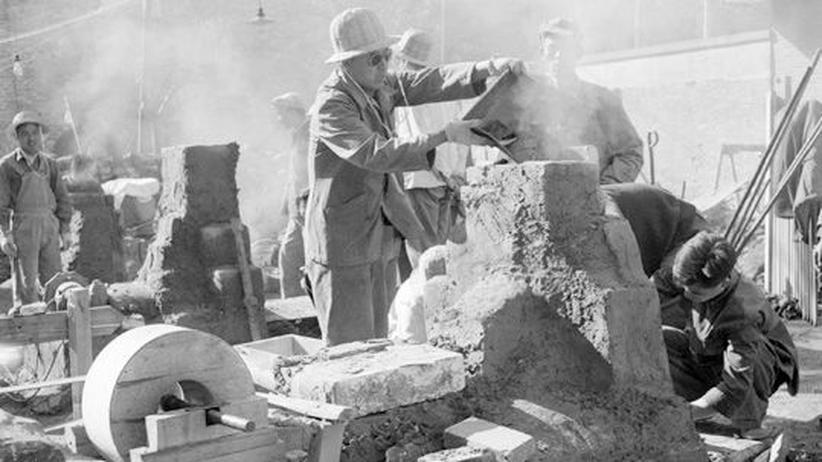 """Mitarbeiter des Pekinger Shin Chiao Hotel bauen im Oktober 1958 einen rudimentären Stahlofen während der Zeit des """"Großen Sprungs""""."""