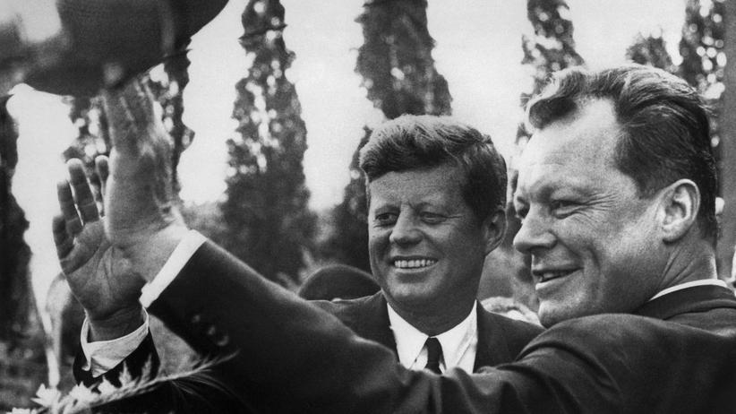 """""""Ich bin ein Berliner!"""": Der US-Präsident John F. Kennedy besucht im Juni 1963 Westberlin. An seiner Seite winkt der damalige Bürgermeister Willy Brandt den Menschen zu."""
