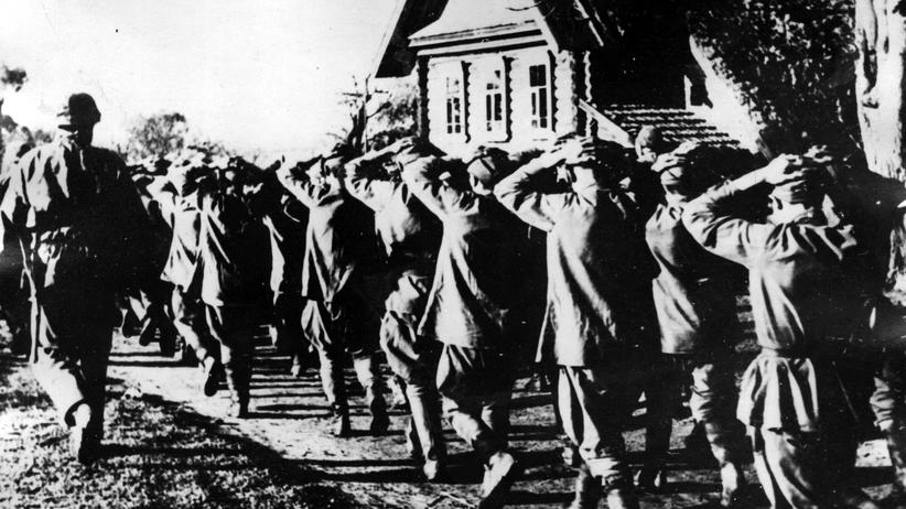Zweiter Weltkrieg: October 1942: A single Nazi paratroop monitors a party of Soviet troops, forced to march with their hands on their heads.