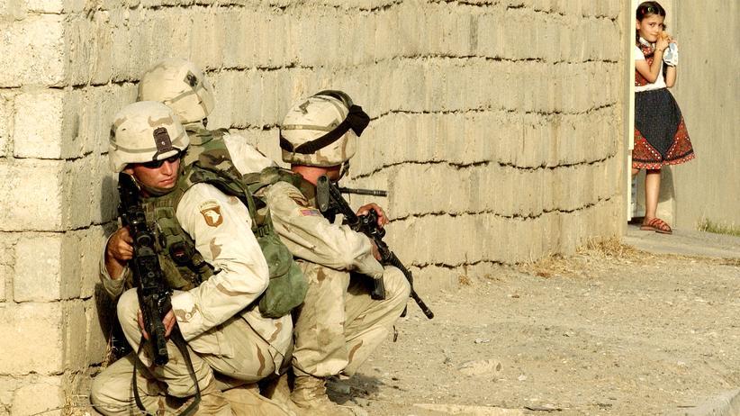 Naher Osten: Ein irakisches Mädchen beobachtet US-Soldaten am 23. Juli 2003, nahe der Stelle, an der am Tag zuvor die Söhne von Saddam Hussein getötet worden waren.