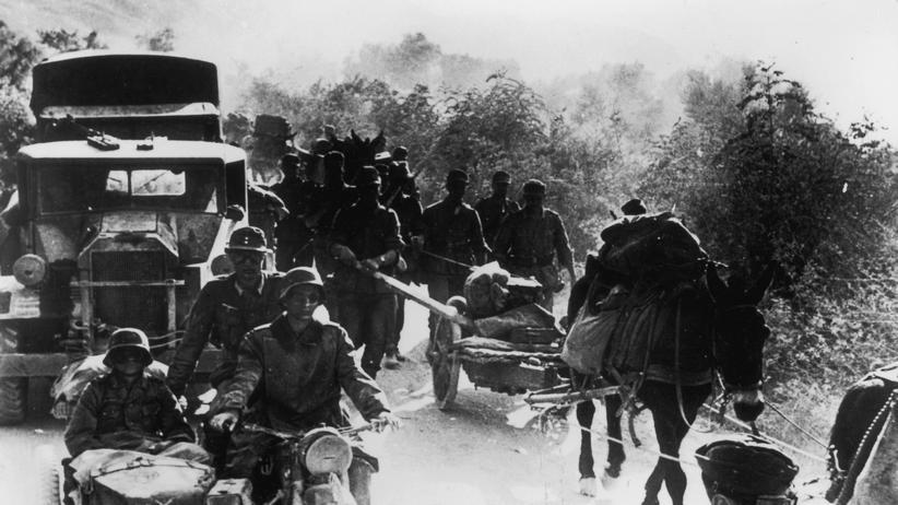Zweiter Weltkrieg: Ein deutscher Militär-Konvoi überholt eine Gruppe griechischer Passanten im Mai 1941, der Anfangsphase der deutschen Besatzung.