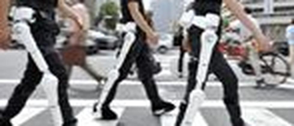 Mitarbeiter von Cyberdyne demonstrieren auf einer Straße in Tokio die Bein-Einheit von HAL