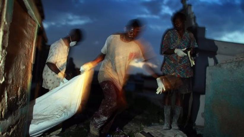 Helfer tragen ein Opfer der Choleraepidemie in Plastiksack zu einem Friedhof in Haitis Hauptstadt Port-au-Prince
