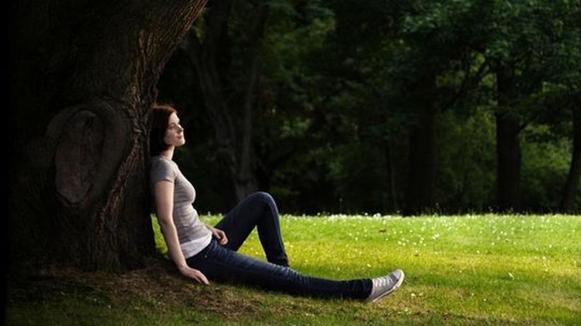 Eine Frau lehnt an einen Baum