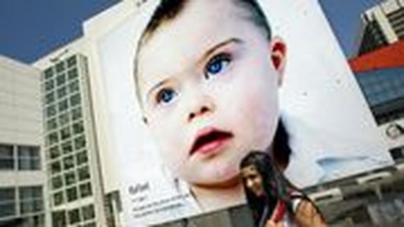 Von einem Plakat in Den Haag schaut ein Kind mit Trisomie 21 hinunter. Die Fotografin Eva Snoijink stellte 2009 Portraits von Kindern mit dem Down-Syndrom aus, um zu zeigen, dass sie ihr Leben genießen.