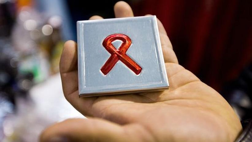 Ein Mann hält eine Tablettendose mit einer roten Schleife in der Hand.