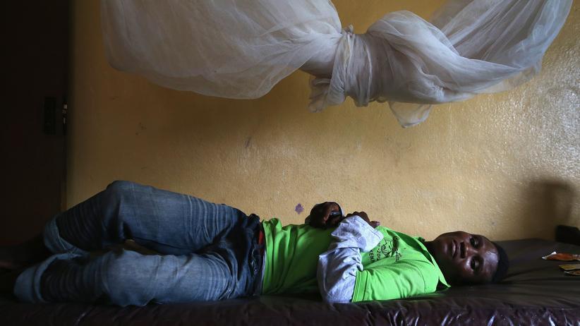 Ein Patient unter einem ungenutzten Moskitonetz in einer Quarantäne-Station in Dolo Town bei Monrovia, Liberia