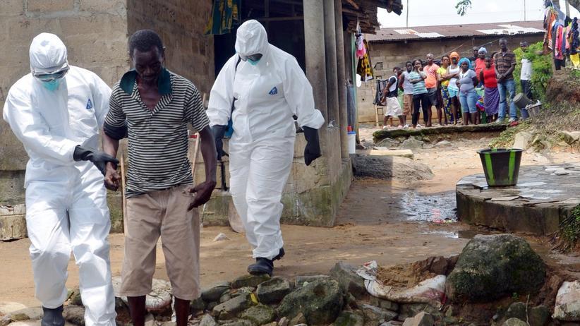 Das Einzige, was hilft: Helfer in Schutzanzügen begleiten im liberianischen Monrovia einen Mann, der sich mit Ebola infiziert haben könnte, zu einer Isolierstation.