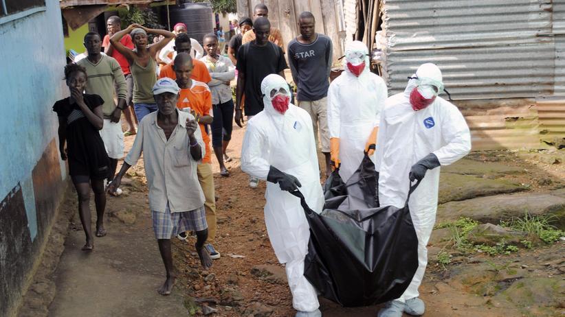 Helfer tragen ein Ebola-Opfer in Liberias Hauptstadt Monrovia davon