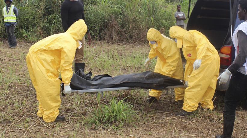 Medizinisches Personal beim Abtransport eines Ebola-Opfers in Sierra Leone.