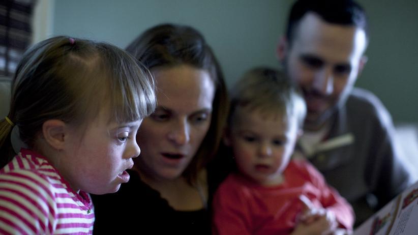 Mutter liest mit ihrer Tochter, die Down Syndrom hat