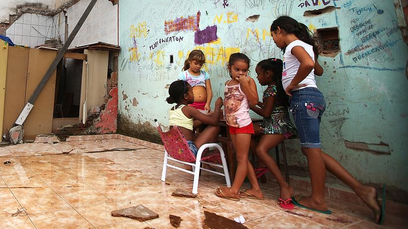 Zika-Virus: Rio de Janeiro im Mai 2014: Kinder spielen in einer der Favelas. Zwischen Schutt sammelt sich Wasser, das Mücken einen optimalen Lebensraum bietet. Und die übertragen nicht nur das Zika-Virus.