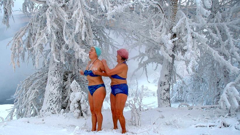 Gesundheit: Eine Frau reibt eine andere mit Schnee ein, nachdem sie bei Minus 26 Grad im sibirischen Jenissei-Fluss gebadet haben.
