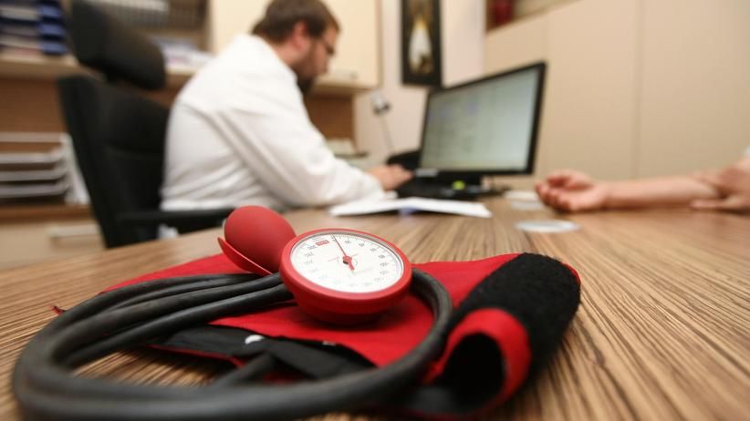 Krankenkasse: BERLIN, GERMANY - SEPTEMBER 05: A doctor speaks to a patient as a sphygmomanometer, or blood pressure meter, lies on his desk on September 5, 2012 in Berlin, Germany.