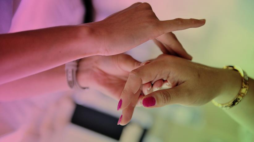 Pflegeprodukte: Eine Verkäuferin reibt ein Pflegeprodukt auf die Haut einer Kundin.