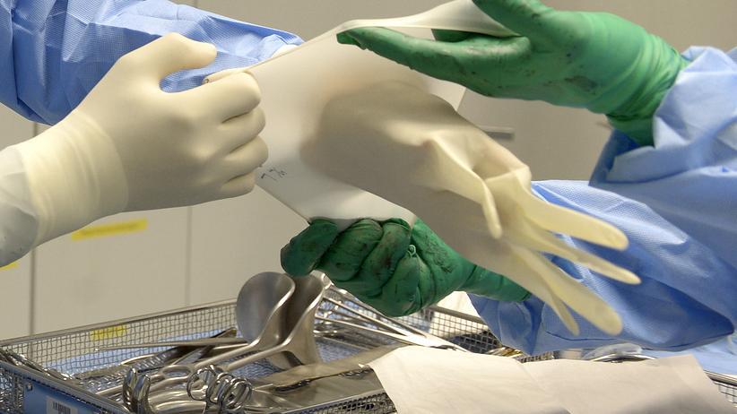 Ärzte: Einem Chirurgen wird beim Anziehen der Handschuhe assistiert.