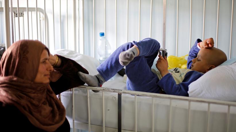 Krebstherapie: Mutter mit ihrem krebskranken Sohn in Damaskus: Wie weit ist die Medizin noch von schonenderen Krebstherapien entfernt?