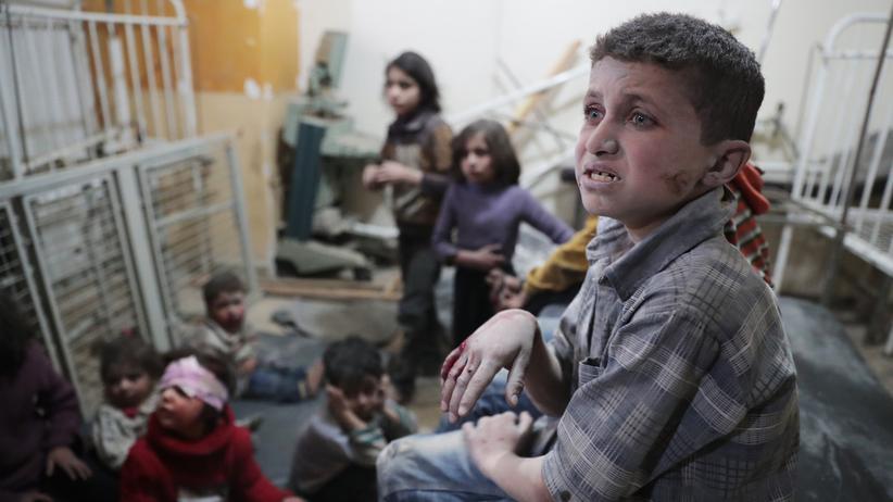 Syrien: Kurz nach einem Bombenangriff warten diese Kinder in der syrischen Stadt Douma darauf, dass sich ein Arzt um sie kümmert.