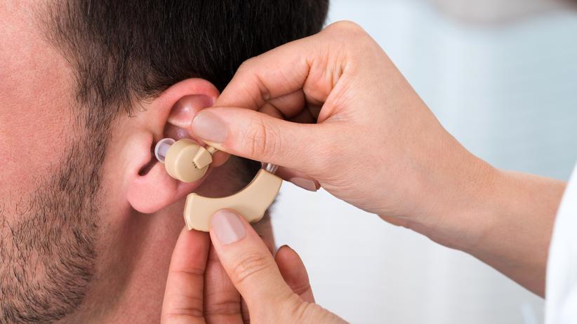 Hörsinn: Eine Ärztin legt einem Patienten ein Hörgerät an. Je früher Hörgeräte zum Einsatz kommen, desto besser bleibt das Gehör erhalten. Auch bei einem irreversiblen Hörsturz.