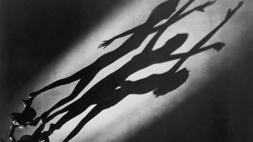 Anorexie: Menschen mit einer Essstörung nehmen ihre Körperkonturen verzerrt wahr. Dieses Bild zeigt die Schatten einer Gruppe von Tänzerinnen um Albertina Rasch, die um die Jahrhundertwende in den USA erfolgreich war.