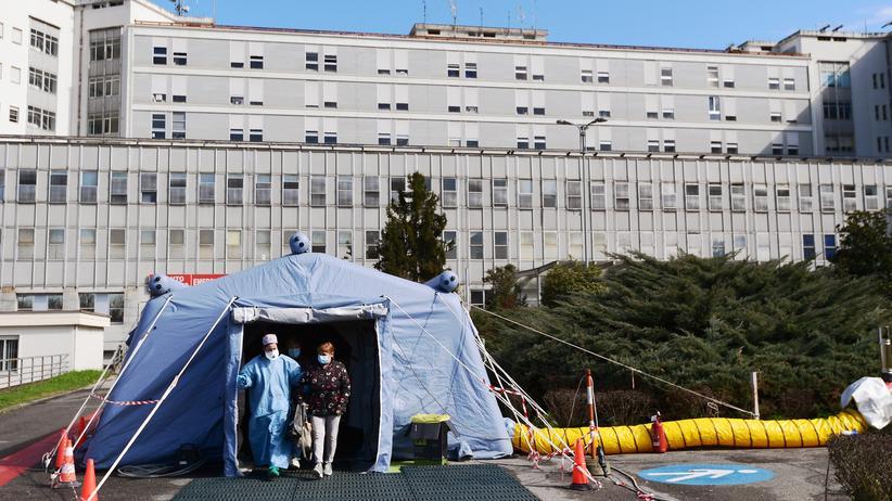 Lombardei: Eine Frau verlässt vor dem Krankenhaus von Cremona in der Lombardei ein sogenanntes Pre-Triage-Zelt, in dem Patienten mit Corona-Verdacht untersucht werden. So hofft man, die Krankenhäuser frei vom Virus zu halten.