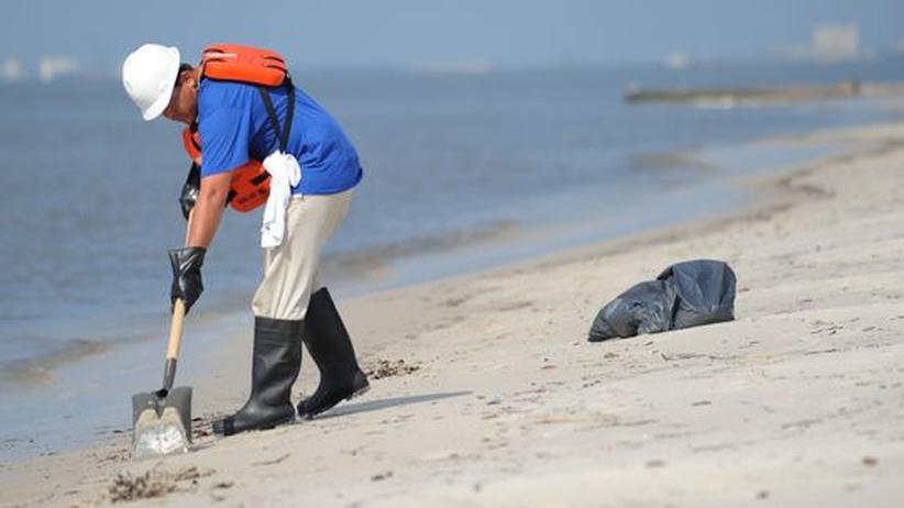 Ein Mann reinigt den Strand in Biloxi vom Öl