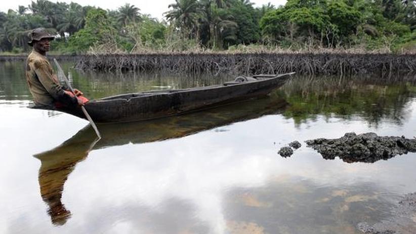 Ein Fischer schaut auf das Rohöl im Nigerdelta
