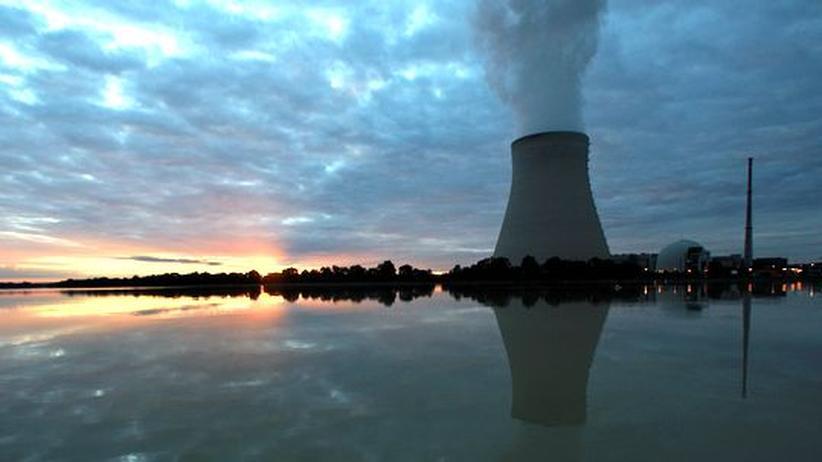 Der Kühlturm des Atomkraftwerks Isar spiegelt sich im Fluss