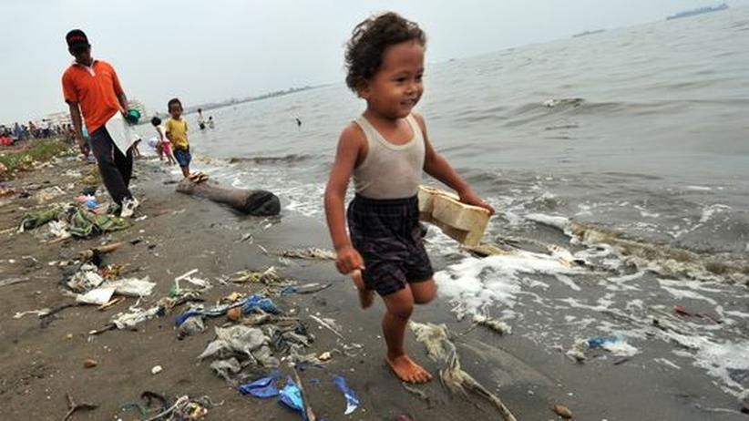 Eine Familie läuft einen verschmutzen Strand in Jakarta entlang