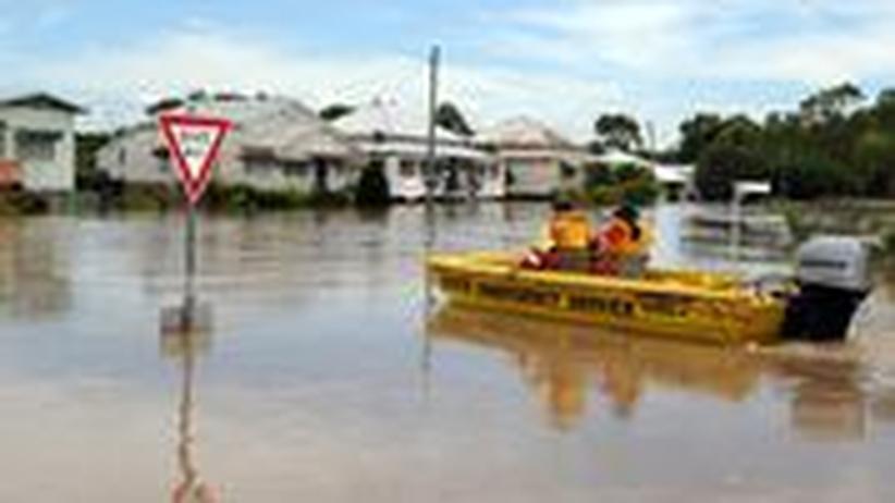 Helfer durchqueren die überfluteten Straßen der Stadt Rockhampton an der Ostküste Australiens. Sie suchen nach Bewohnern, die die Stadt noch nicht verlassen haben
