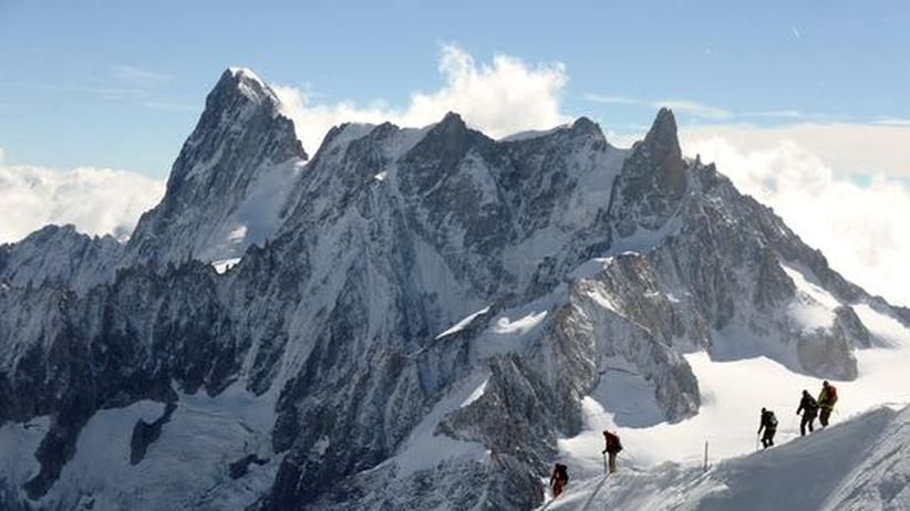 Blick auf die Grandes Jorasses (mehr als 4200 Meter hoch) im Mont-Blanc-Massiv der Alpen, an der Grenze zwischen Frankreich und Italien. Im Vordergrund sind Bergsteiger auf dem Aiguille du Midi zu sehen