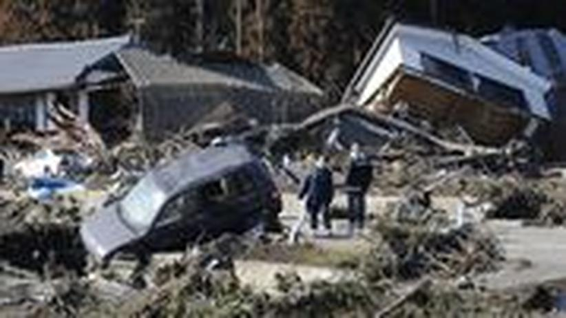 Menschen blicken auf die Trümmer ihrer Stadt. Wenig hat das Beben und der Tsunami vom 11. März 2011 in Minamisoma in der Präfektur Fukushima verschont.