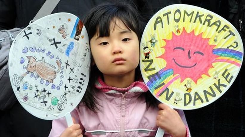 Ein Mädchen hält im Februar in Tokio Plakate auf einer Anti-Atomkraftdemonstration hoch.