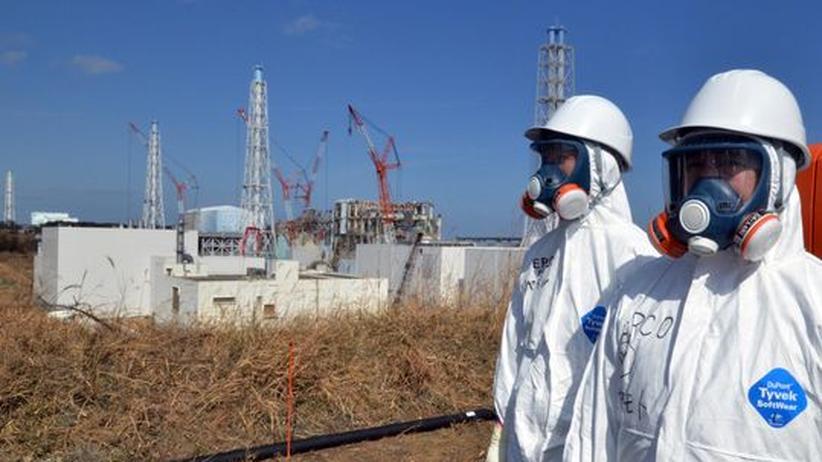 Arbeiter des AKW-Betreibers Tepco stehen Ende Februar 2012 vor den havarierten Reaktoren von Fukushima-Daiichi.