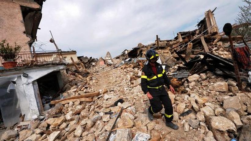 Keine Woche nach dem Beben vom 6. April 2009 läuft ein Feuerwehrmann durch die Trümmer eines Hauses in L'Aquila.