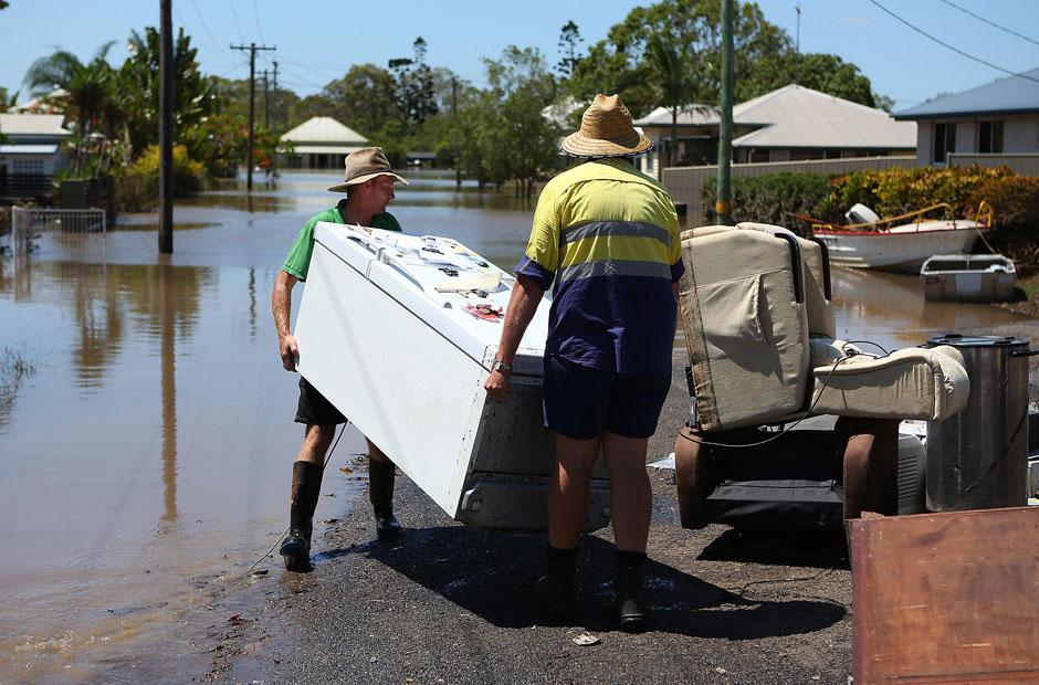 Bewohner räumen fortgeschwemmte Möbel und Geräte von den Straßen.