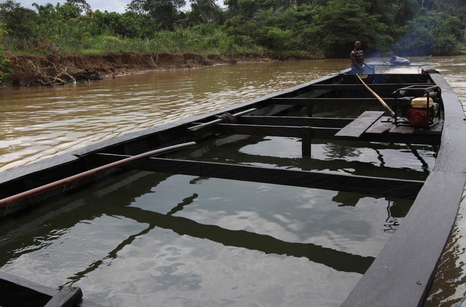Per Boot bringt ein Mann das Rohöl zur Raffinerie am Fluss Nun.