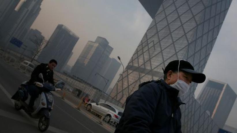 Smog-Nebel ist in Chinas Hauptstadt keine Seltenheit. Viele Menschen tragen Mundschutz, wie dieser Mann im Finanzviertel von Peking.